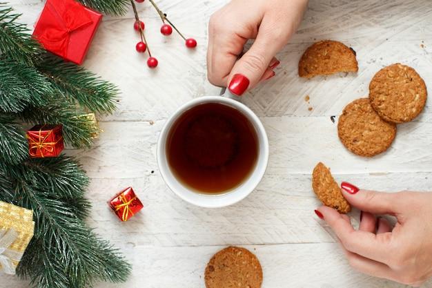 Новогодняя композиция с руками, держащими кружку чая и печенье