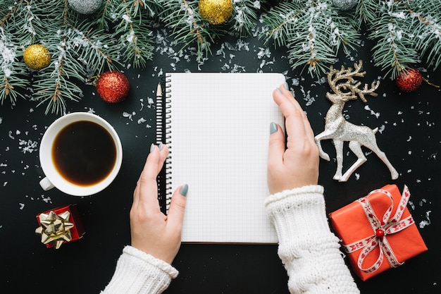 Christmas composition with hands touching notepad