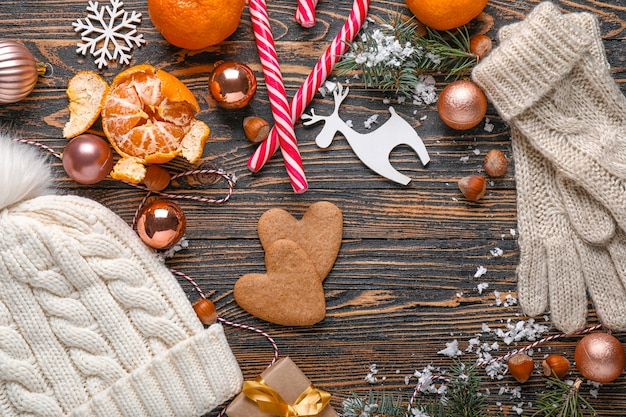 Christmas composition with hat and gloves on wooden background