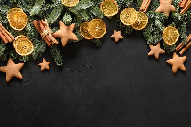 Новогодняя композиция с праздниками домашнее печенье, ароматные апельсиновые чипсы, вечнозеленые ветки на черном фоне. с новым годом. вид сверху. плоская планировка.
