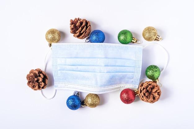 医療用フェイスマスクとカラフルなボール、白い背景の上の装飾品の装飾とクリスマスの構成