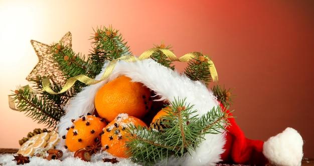 Новогодняя композиция с апельсинами и елкой в шапке деда мороза
