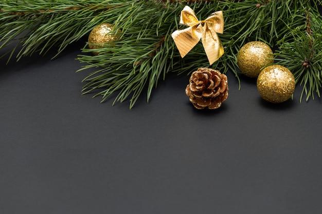 暗い背景に金色のボールと松ぼっくりで飾られた松の枝のクリスマスの構成