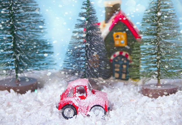 Christmas composition with pine trees and toy red car.