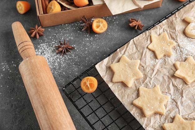 회색 배경에 원시 쿠키와 롤링 핀이 있는 크리스마스 구성