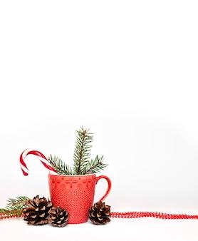 赤いマグカップ、松ぼっくり、モミ針のクリスマス組成物。白い表面に分離されました。コピースペース