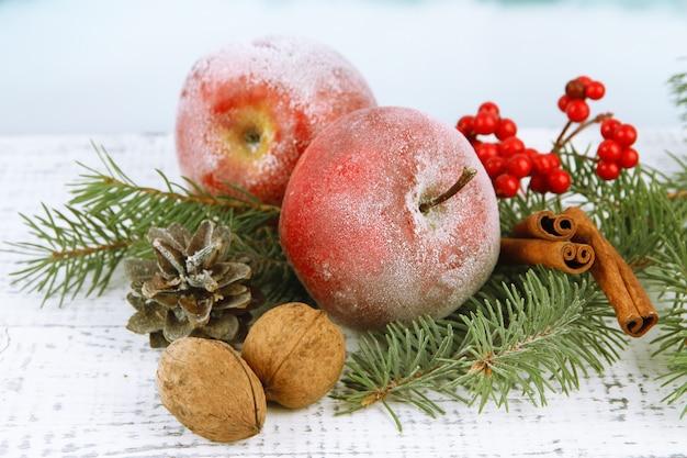 テーブルの上の赤い冬のリンゴとクリスマスの構成をクローズアップ