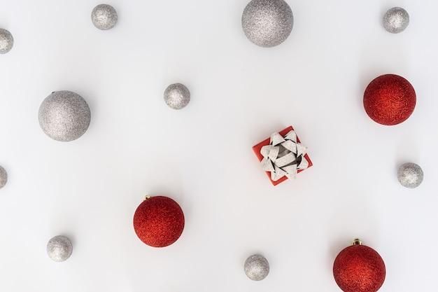 은색과 빨간색 크리스마스 공과 흰색에 깜짝 선물 상자가 있는 크리스마스 구성