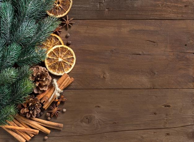 Рождественская композиция со специями и ветвями на деревянном столе с копией пространства вид сверху