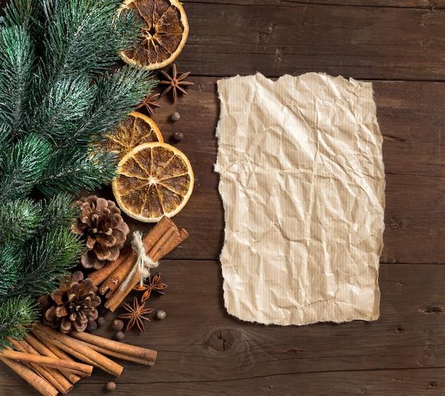 Рождественская композиция со специями, ветвями и бумагой на деревянный стол с копией пространства вид сверху