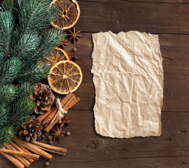Christmas composition with spices, branches and paper on wooden table with copy space top view