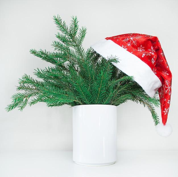トウヒとサンタの帽子のクリスマス作曲。メリークリスマスカード。冬の休日のテーマ。