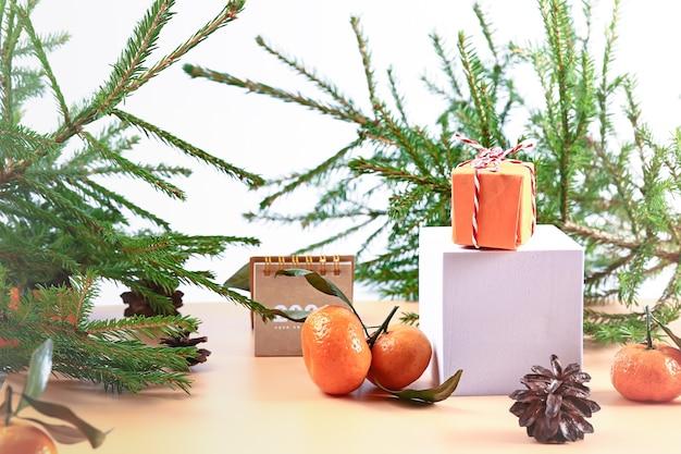 Новогодняя композиция с еловыми мандаринами подиум и блокнотом мягкий выборочный фокус зимний праздничный ...