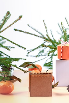 Christmas composition with spruce, tangerines, podium and notepad. soft selective focus. winter festive background.