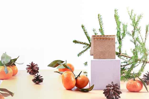 Christmas composition with spruce tangerines podium and notepad soft selective focus winter festive ...