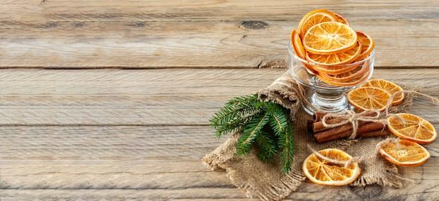 Рождественская композиция с еловыми ветками, палочками корицы и гирляндой из сушеных ломтиков апельсинов на деревянных фоне. деревенский стиль. баннер.
