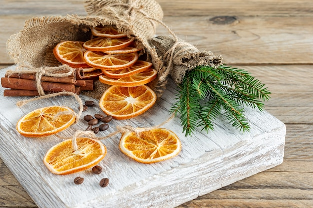 Рождественская композиция с еловыми ветками, палочками корицы и гирляндой из сушеных ломтиков апельсинов на деревянных фоне. деревенский стиль.