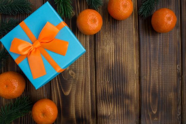 茶色の木の背景にみかんとギフトのクリスマスの構成。上面図。コピースペース。