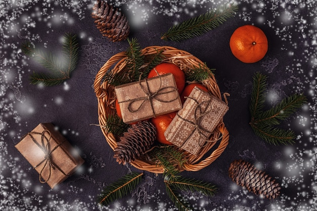 Christmas composition with tangerines, gift boxes, cones on dark  background.