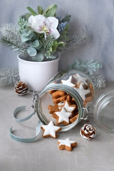 Christmas composition with tasty star ginger cookies in a glass jar with winter floral decorations