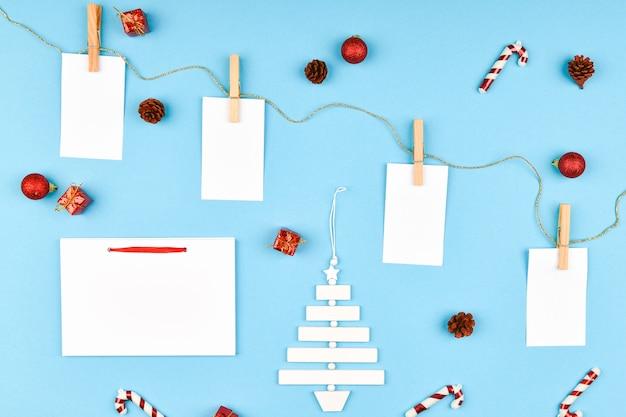 書くためのさまざまなオブジェクトとクリスマスの組成物。クリスマススペースを撮影したスタジオ。空の葉のレイアウト。執筆のための場所。上からの眺め。青い空間に。