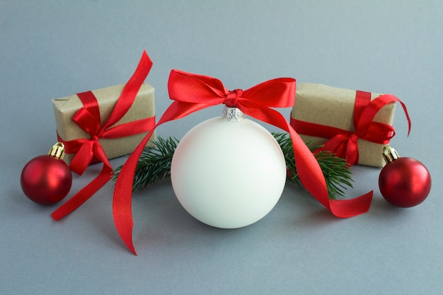 Christmas composition with white ball, branches of spruce and gift box on the gray background. close-up.