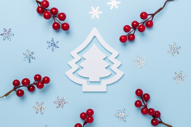 Christmas composition with white fir tree, holly berries and snowflakes on pastel blue background