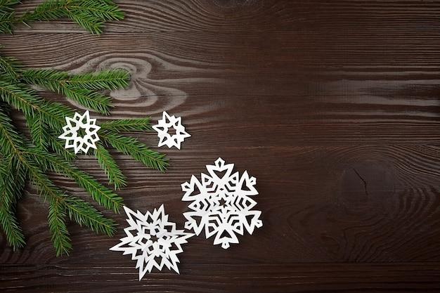 Рождественская композиция со снежинками из белой бумаги и еловой веткой на деревянном