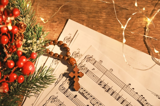 Christmas composition with wooden cross and music sheets on table