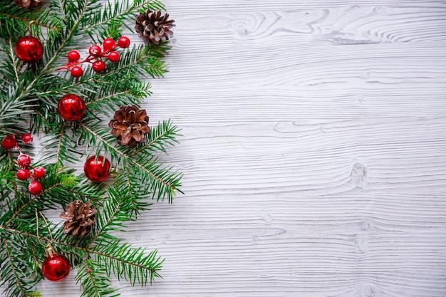 白いテーブルの上のクリスマスツリーと赤い果実とクリスマスの構成