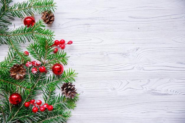 白いテーブルにクリスマスツリーと赤い果実のクリスマスの構成。