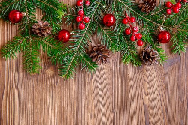 木製のテーブルにクリスマスツリーと赤い果実とクリスマスの構成