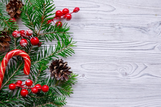 Christmas composition with xmas tree and red berries on white table