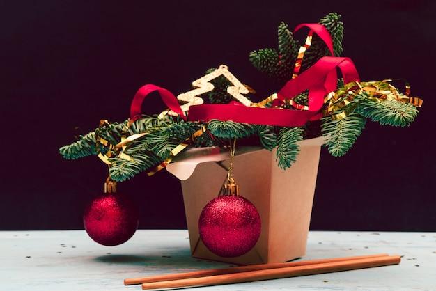 クリスマスの組成物。中華鍋の紙箱。クリスマスツリーと装飾。