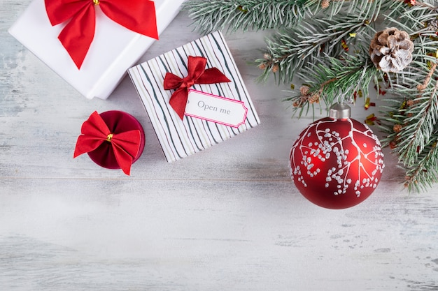 Christmas composition on a wooden  covered in white snow. christmas gift boxes with red bows, snowy fir branches,  holiday decoration with red ball.