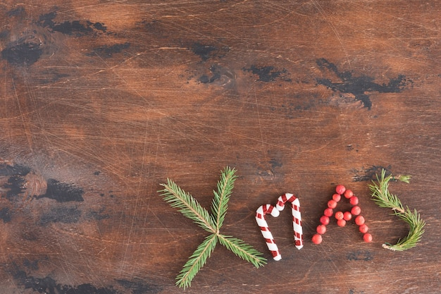 Christmas composition on wooden dark background. christmas xmas text, pine cones, fir branches on wood desk, flat lay and top view, copy space