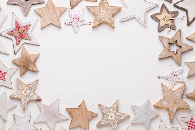 クリスマスの作文。木製の装飾、白い背景の上の星。クリスマス、冬、新年のコンセプト。フラットレイ、上面図、コピースペース。