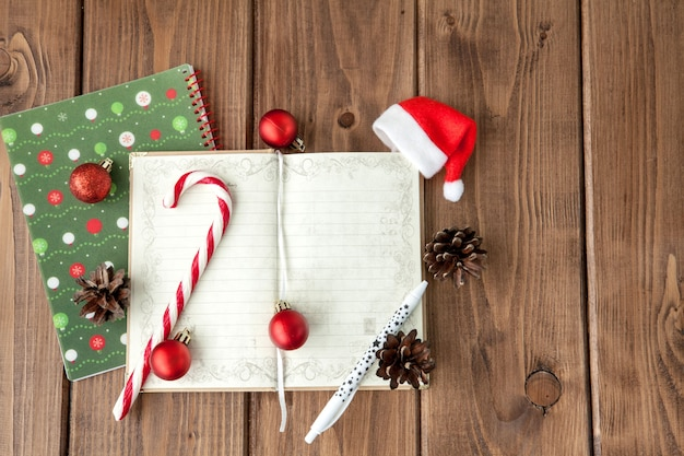 Christmas composition on a wooden table with notebook with plans for the year.