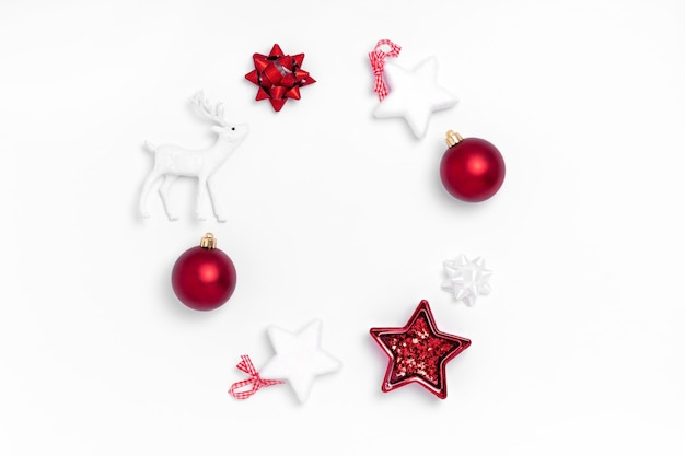 Christmas composition. wreath from red balls, white stars, deer on white paper background.