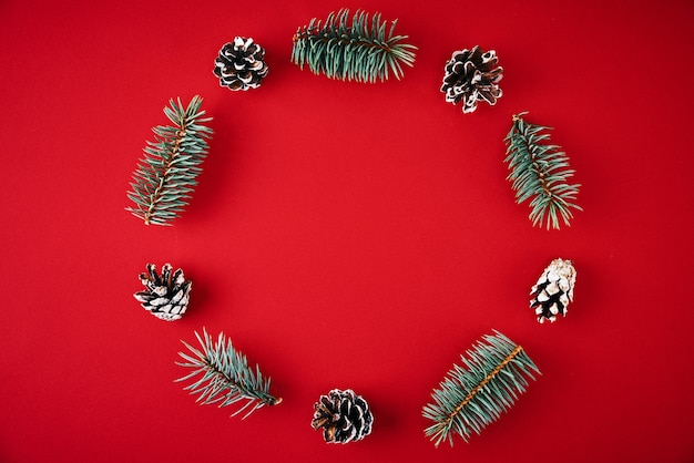 Christmas composition. wreath made of fir tree branches and festive pine cones on red background, top view
