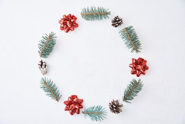 Christmas composition. wreath made of fir tree branches and festive pine cones on white background, top view