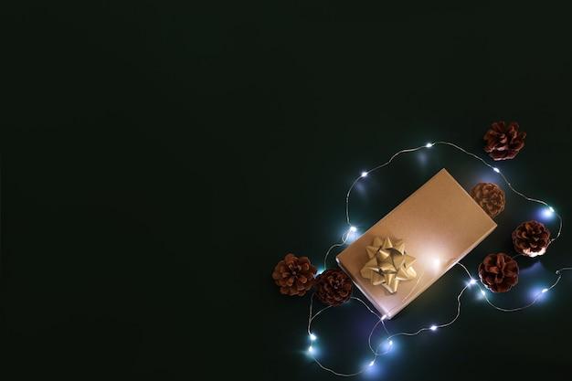 Новогодняя композиция. рождественский фон. рождественский подарок и элементы декора на темном фоне, гирлянды. свободное место для текста, копировальное пространство. плоская планировка, вид сверху