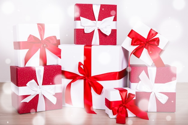 Christmas concept - close up of red and white gift boxes on wooden floor