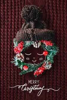 常緑のトウヒのニット帽とイラストのリースから作られたクリスマスのコンセプトのかわいい赤ちゃん...