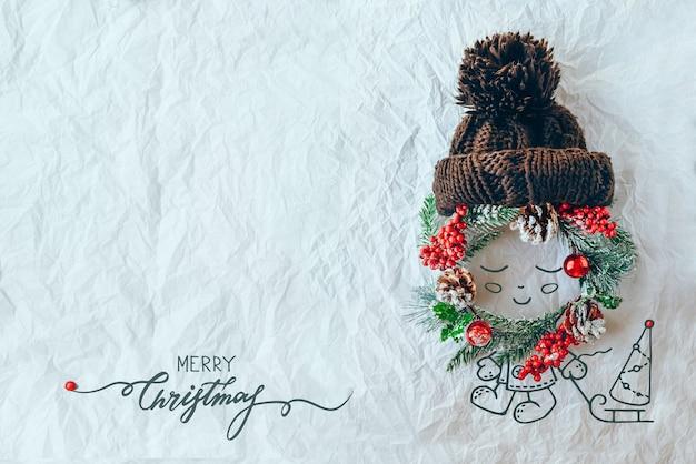 クリスマスのコンセプト。常緑のトウヒの花輪、ニット帽、白い背景のイラストで作られたかわいい赤ちゃん。最小限の冬休みのアイデア。フラットレイトップビュー構成。