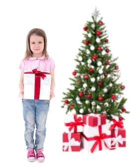 Christmas concept - cute little girl with gift box and christmas tree isolated on white background