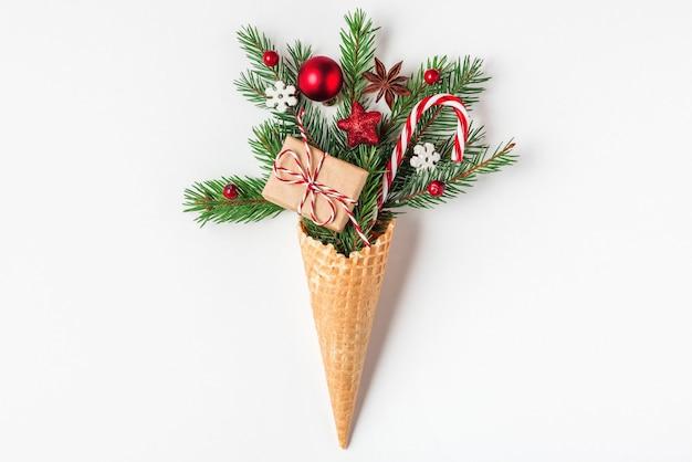 クリスマスのコンセプト。白い背景の上のワッフルアイスクリームコーンのモミの木の枝、ギフトボックス、クリスマスの装飾。上面図。フラットレイ