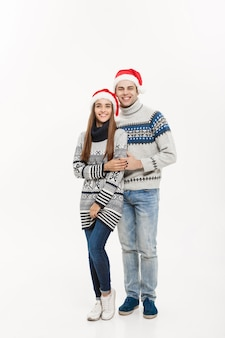 クリスマスのコンセプト-クリスマスの日を祝う抱擁を与えるフルレングスの若い魅力的な白人カップル。