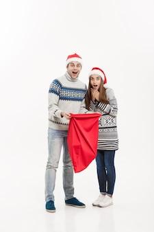 クリスマスのコンセプト-白い灰色の壁に分離されたサンタバッグを保持しているフルレングスの若い魅力的なカップル。