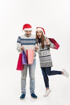 クリスマスのコンセプト-白い灰色の壁に分離された買い物袋を保持しているフルレングスの若い魅力的なカップル。